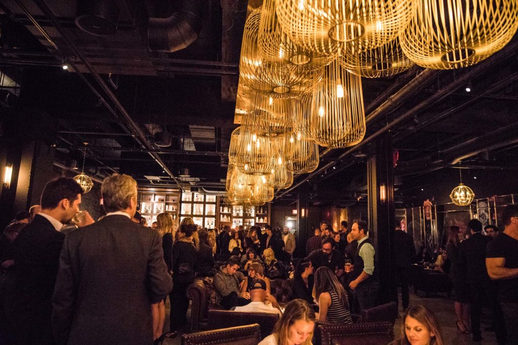 large filament bulbs light a dark underground lounge filled with well dressed patrons