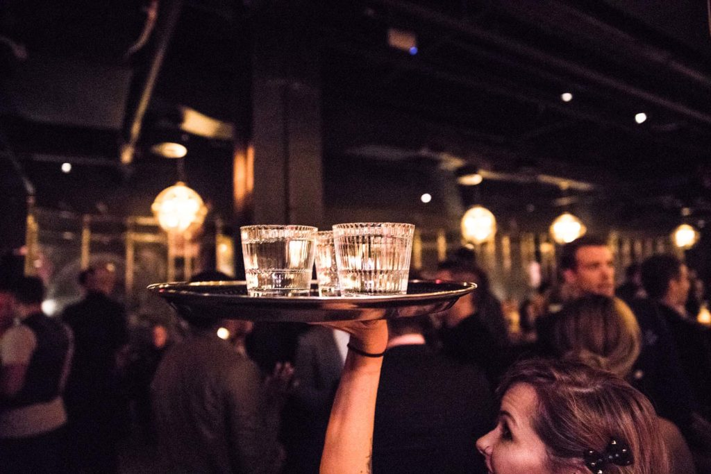 a server carrying a tray of drinks through a dark underground lounge