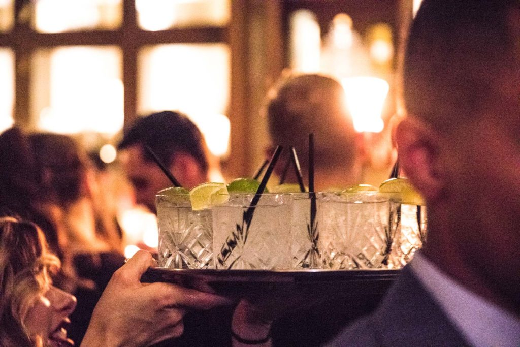 a server carrying a tray of drinks in crystal glasses garnished with lime wedges