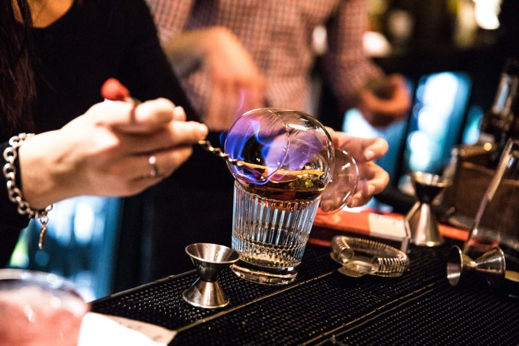 a bartender mixing a cocktail that is on fire with blue flames