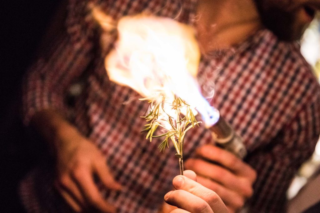 a bartender lighting fresh rosemary on fire with a blow torch