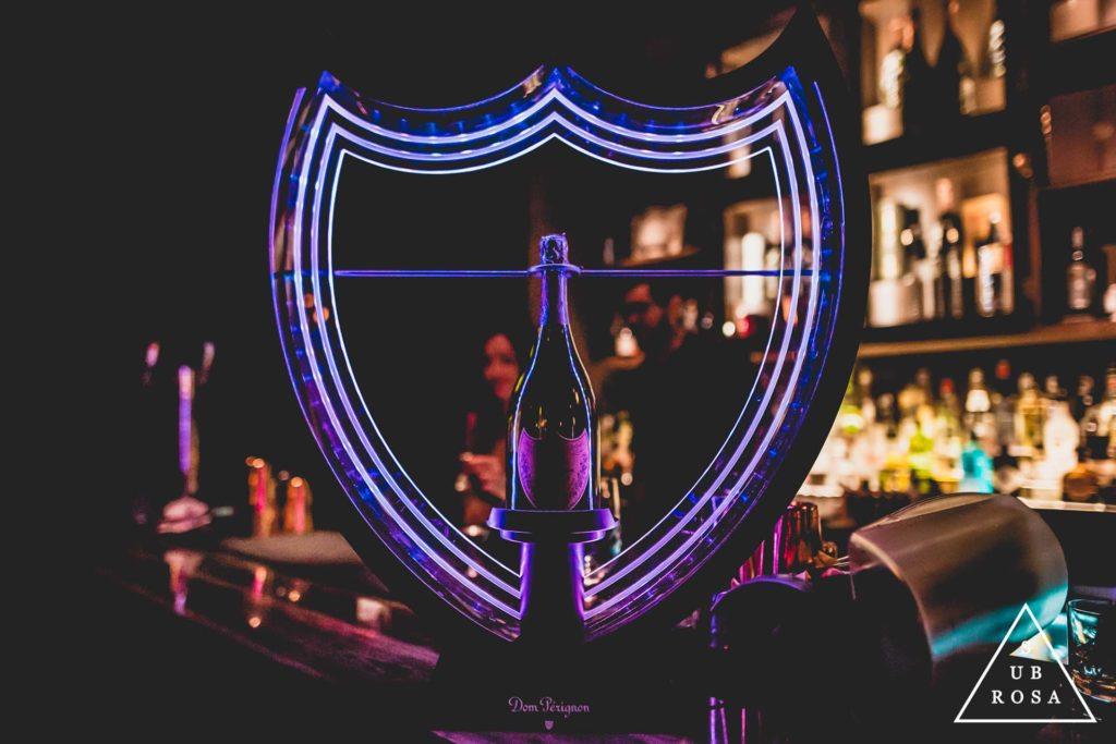 a bottle of Dom Perignon enclosed in a neon light shield-shaped holder