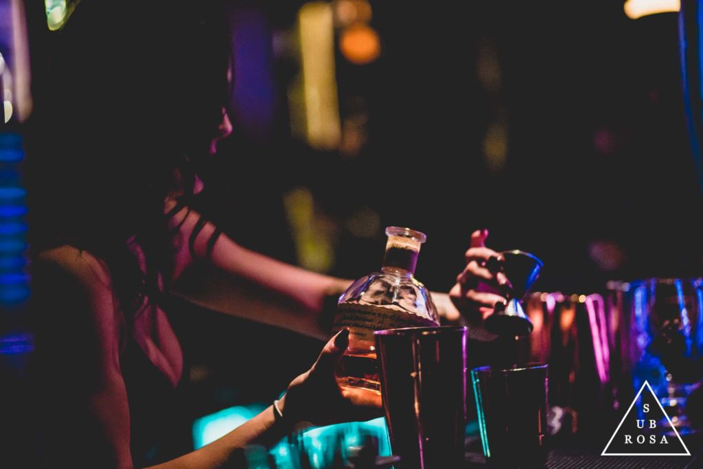 a bartender pouring a shot from a bottle of whisky in a dark underground lounge