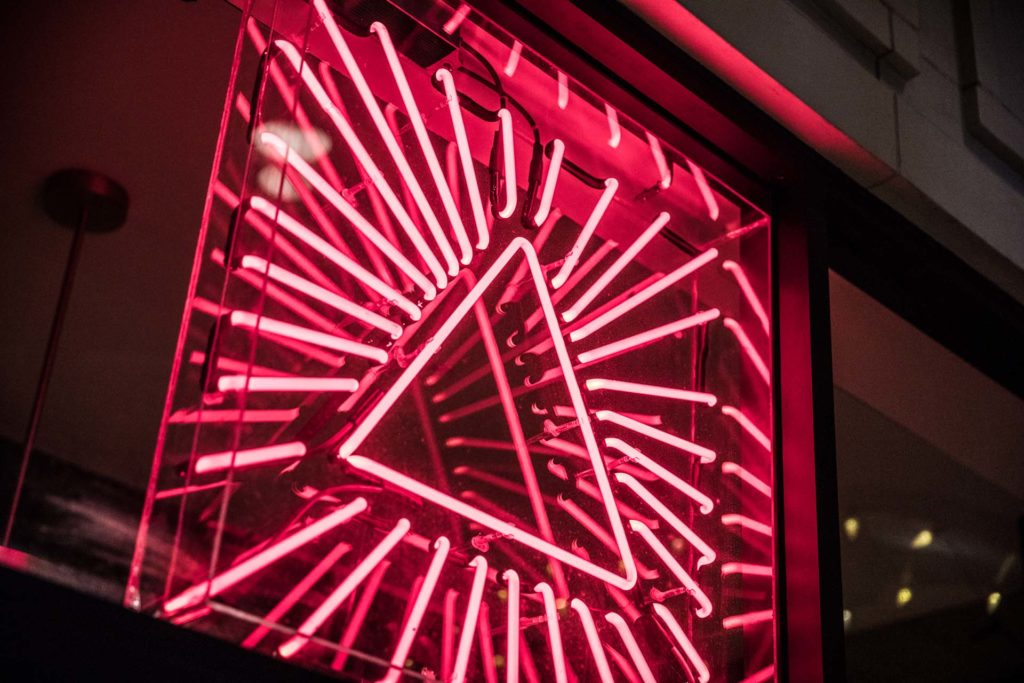A pink neon sign of a triangle with straight lines pointing outward from it