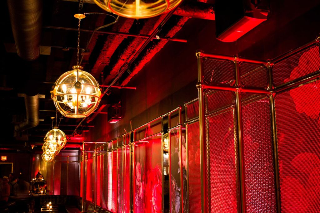 atmospheric red walls with hanging globe lights in an underground speak-easy lounge