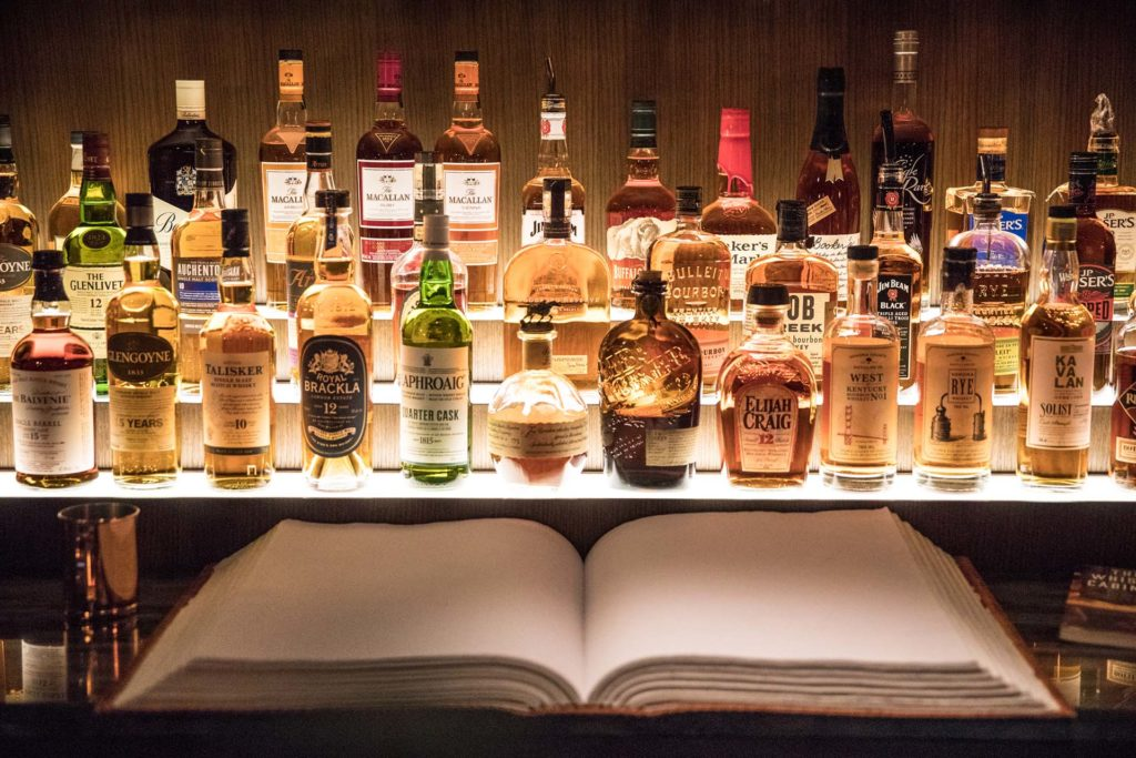 a lit up back bar filled with bottles of whisky