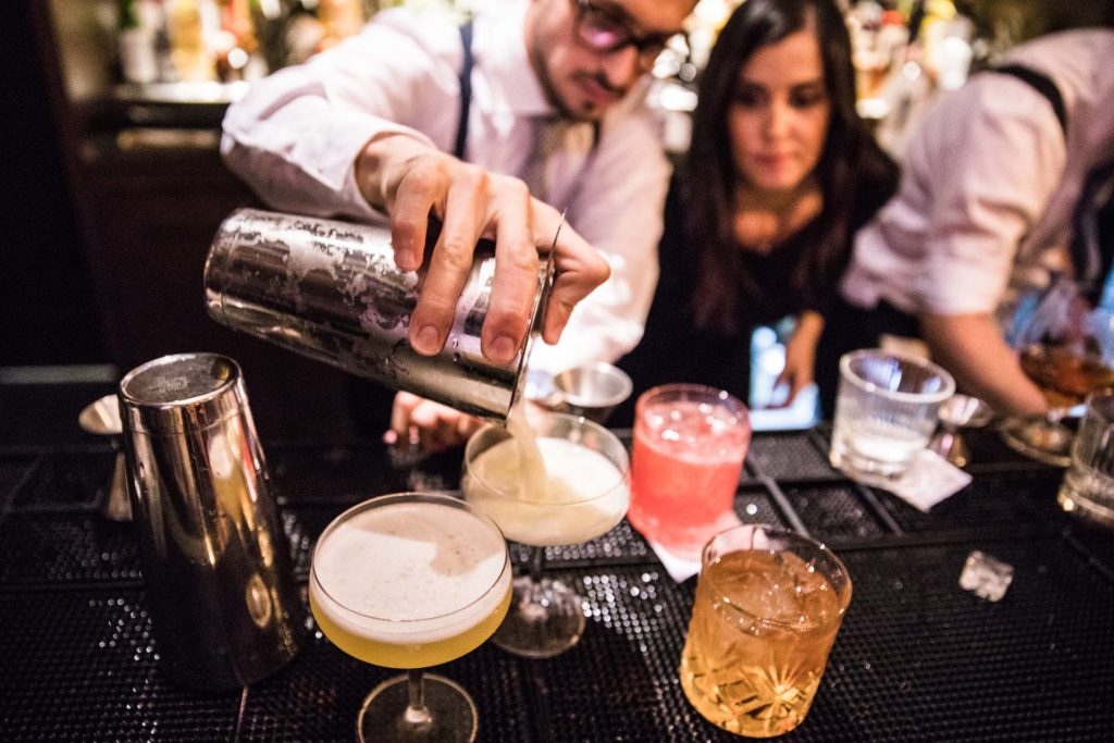 a bartender pouring a craft cocktail out of a shaker into a glass