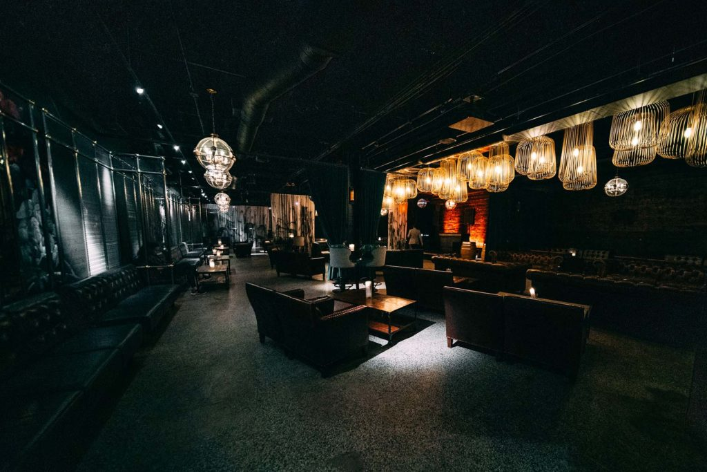 Large filament bulbs hang from the ceiling of a spaceous dimly lit underground lounge