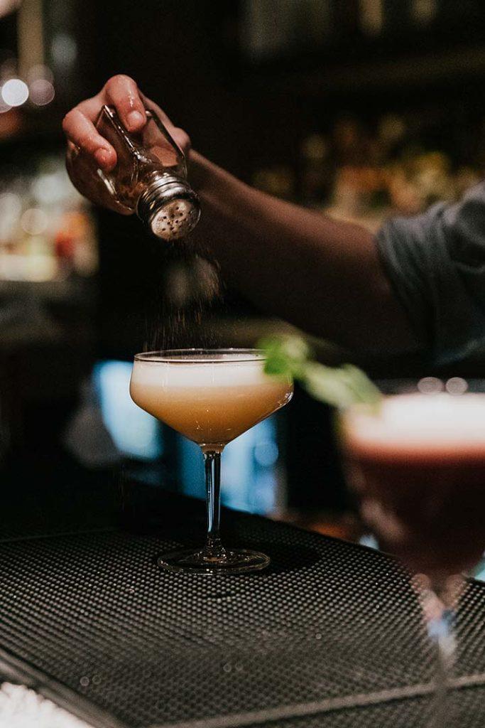 a bartender shaking salt into a craft cocktail