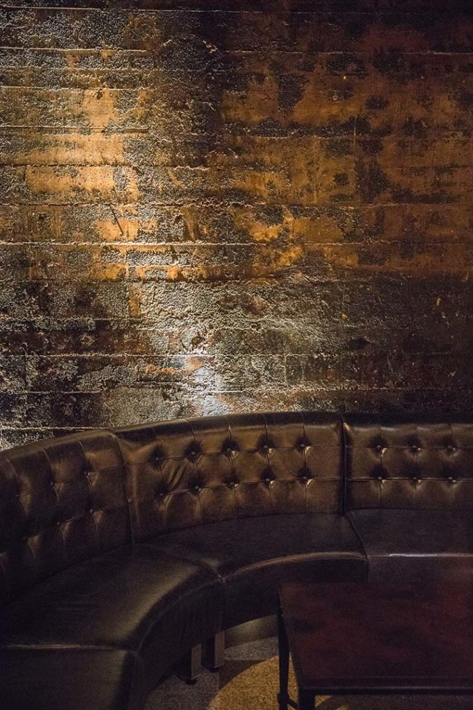 black leather couch against a textured brick wall