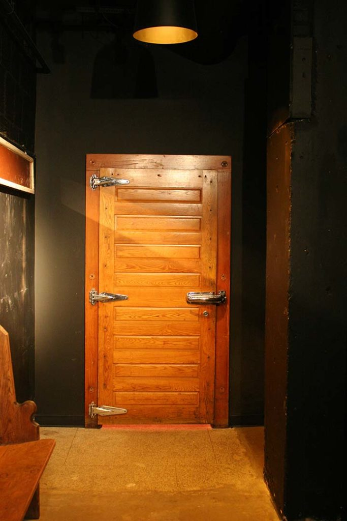 a wooden door leading to a speak-easy style underground lounge