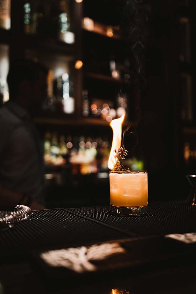 a craft cocktail with a flaming garnish