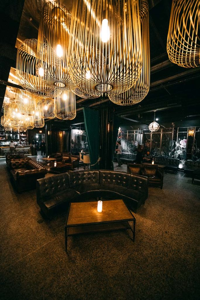 large filament bulbs over top of leather couches in a dark underground lounge