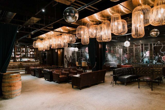 Large filament bulbs hang from the ceiling of a dimly lit underground lounge
