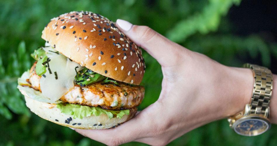 Teriyaki Salmon Burger held in front of greenery.