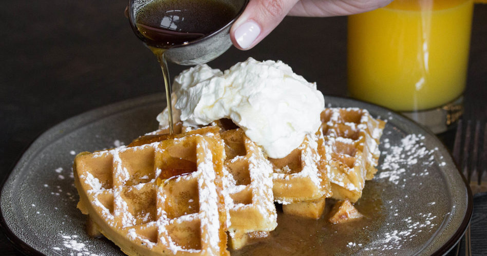 Hand pouring syrup on waffles