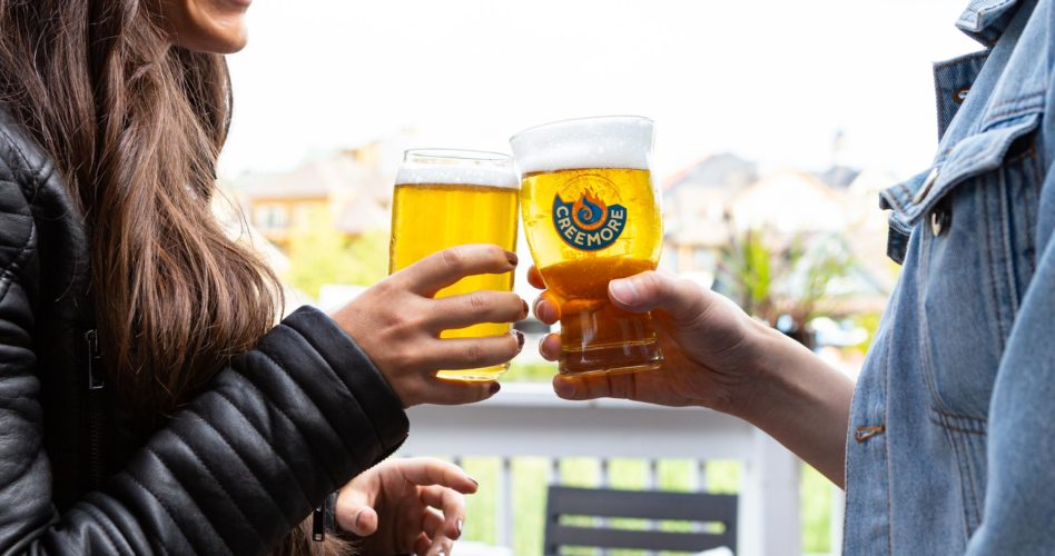Two guests cheersing glasses of beer