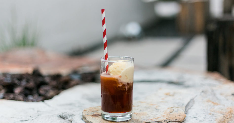 Root beer float in a clear glass with a red and white straw.