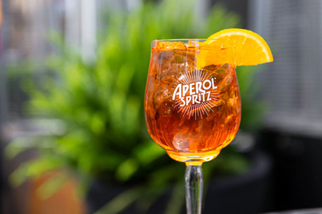 Aperol Spritz glass garnished with an orange slice.