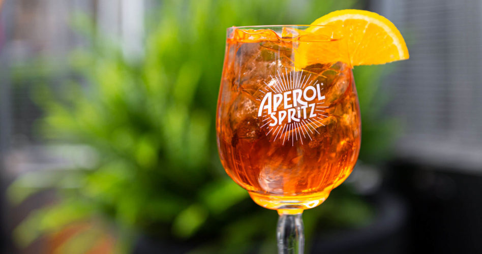 Aperol Spritz glass garnished with an orange slice.