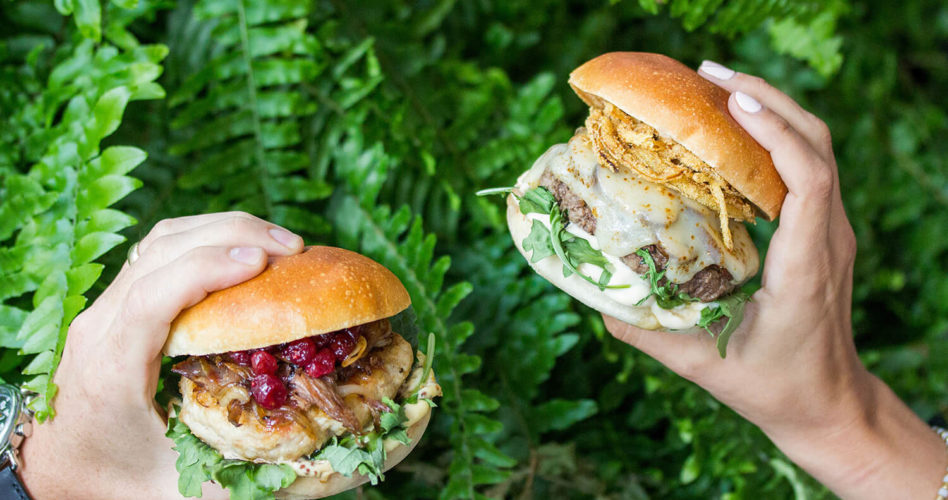 Two hands holding burgers against a foliage backdrop