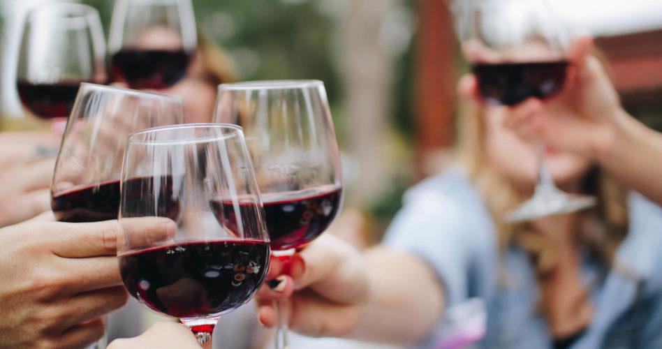 Group of people cheersing wine glasses.
