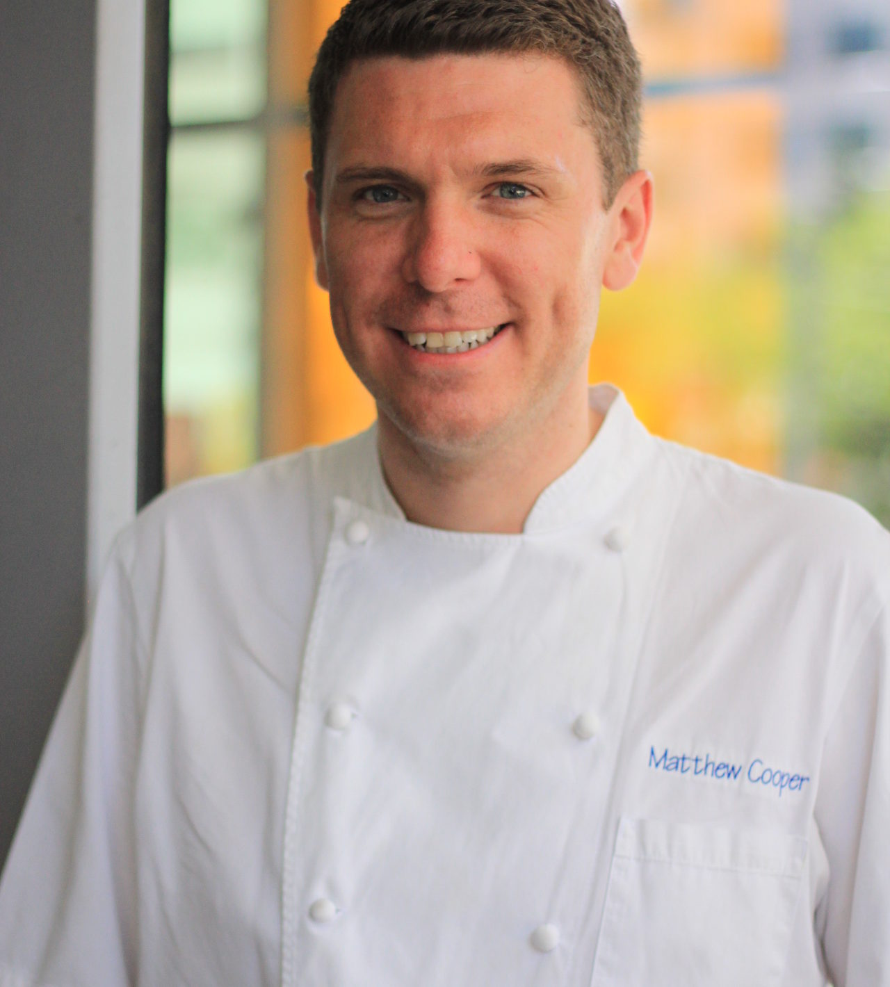 Chef Matthew Cooper standing in front of a window wearing a white uniform