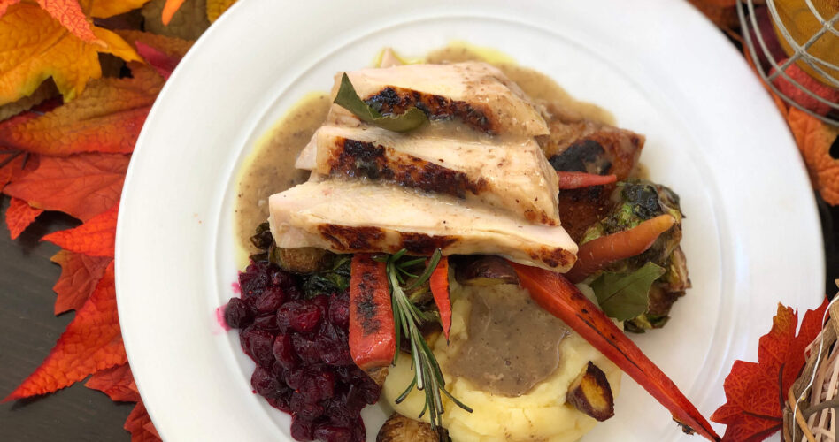 Turkey, potatoes, gravy, roasted vegetables and cranberry sauce on a white plate