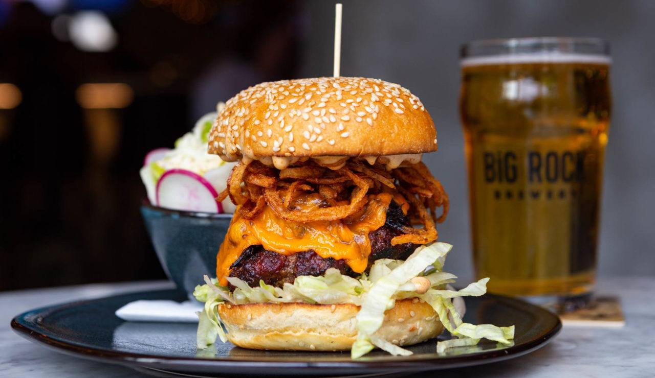 TFC Burger - Liberty Commons Liberty BBQ Burger with quarter-pound beef brisket burnt ends smoked cheddar crispy onions sweet and smoky aïoli with Big Rock Beer and side salad