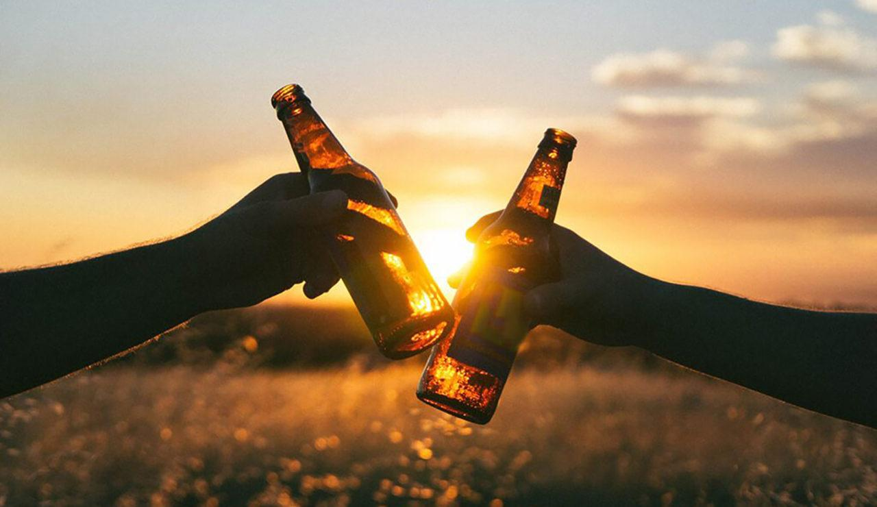 Two people clinking beers before a sunset