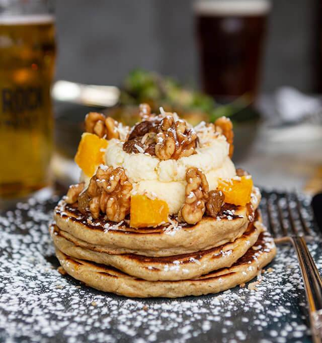 CARROT CAKE PANCAKES - smoked buttercream frosting, walnuts, tea raisins, orange, coconut