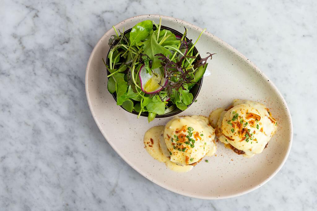 P.E.I. ROCK CRAB CAKE BENNY - poached eggs, Old Bay Hollandaise, green salad