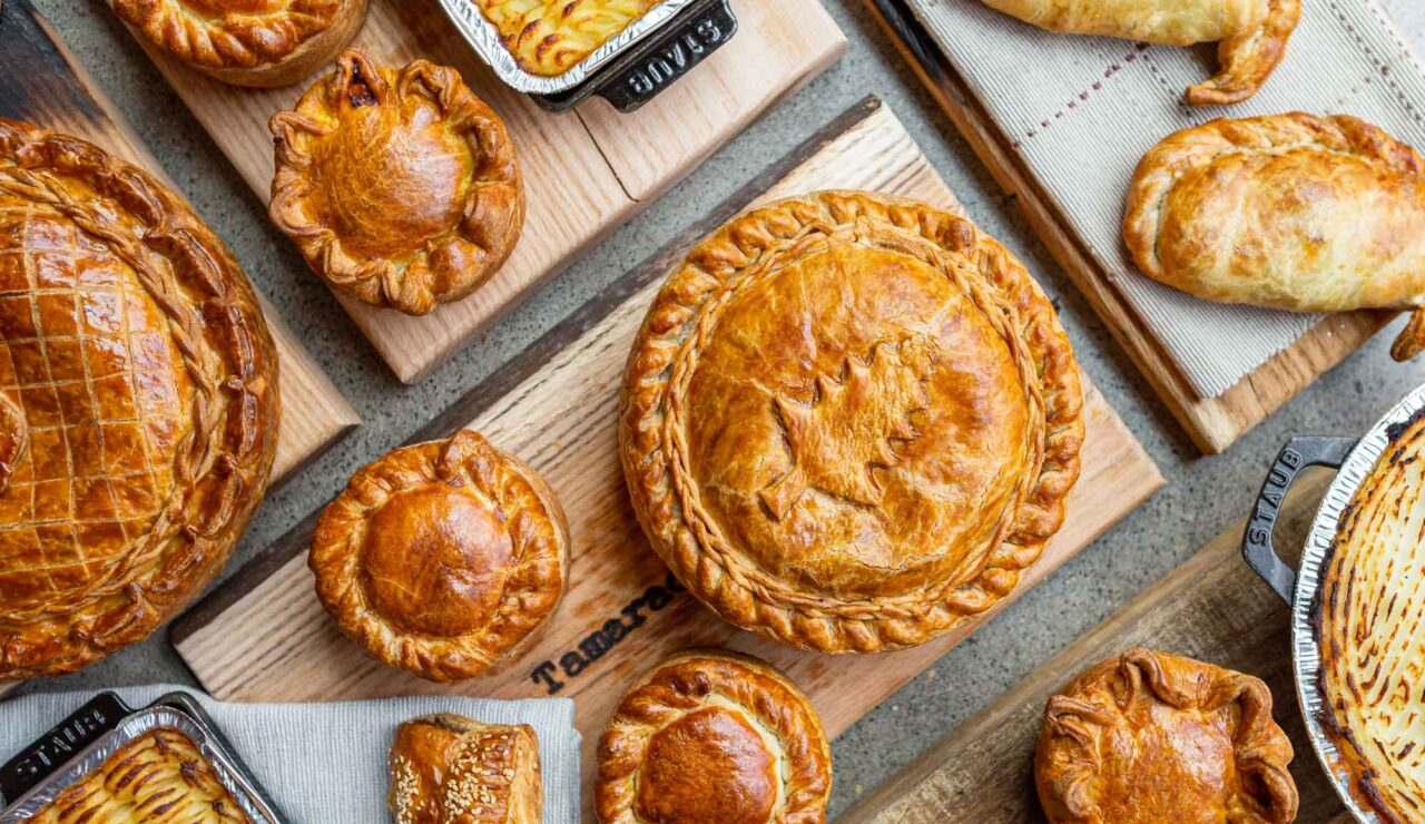 variety of pies on wooden boards