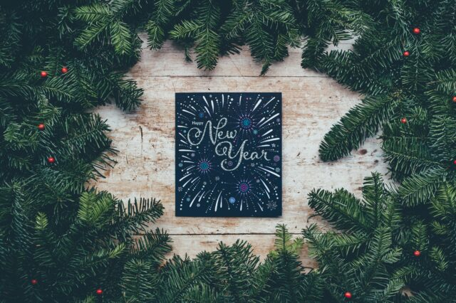 Happy New Year chalkboard sign on wooden backdrop, surrounded by pine tree leaves