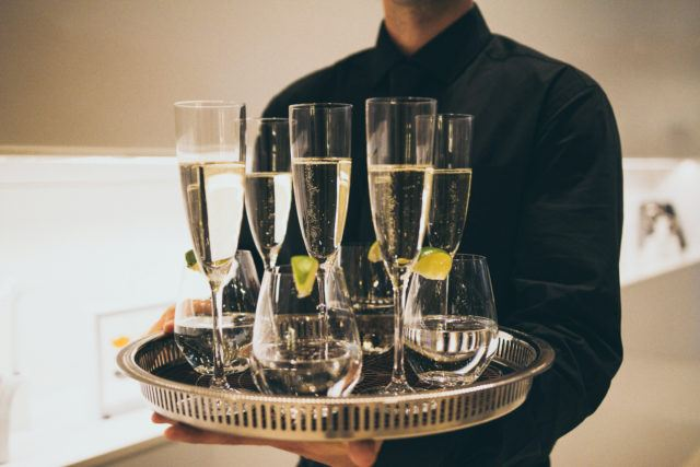 Server holding a tray of champagne flutes and glasses of water