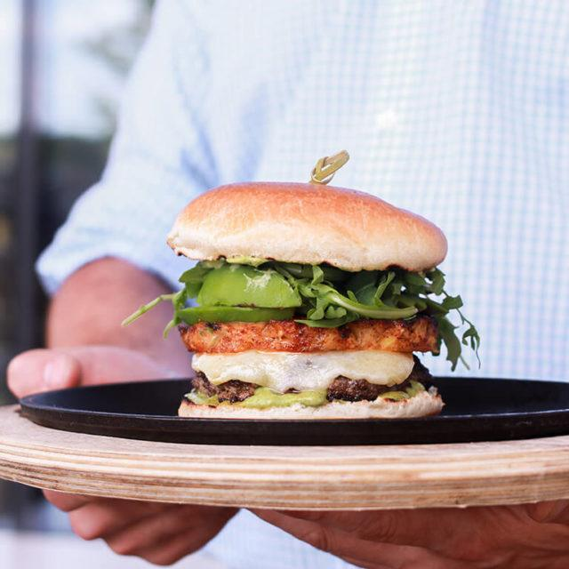 Special Shift burger for Le Burger Week festival. Burger with spiced pineapple, white cheddar, avocado, and baby arugula. On a wooden serving tray being held by a man.