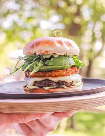 Special Shift burger for Le Burger Week festival. Burger with spiced pineapple, white cheddar, avocado, and baby arugula. On a wooden serving tray being outwards with trees in the background.