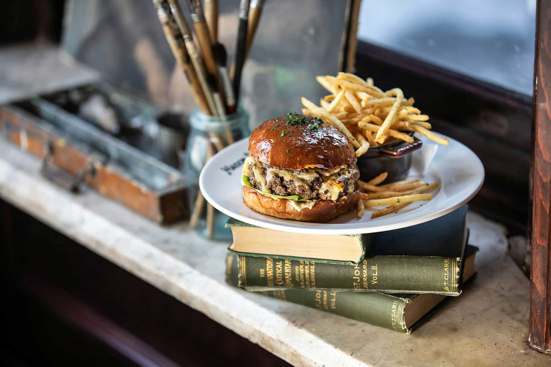 Maison Selby French Onion Burger with fries sitting on a stack of books
