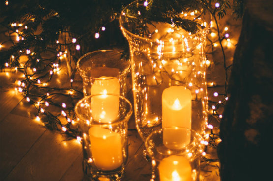 Candles in glass holders surrounded by twinkle lights and greenery