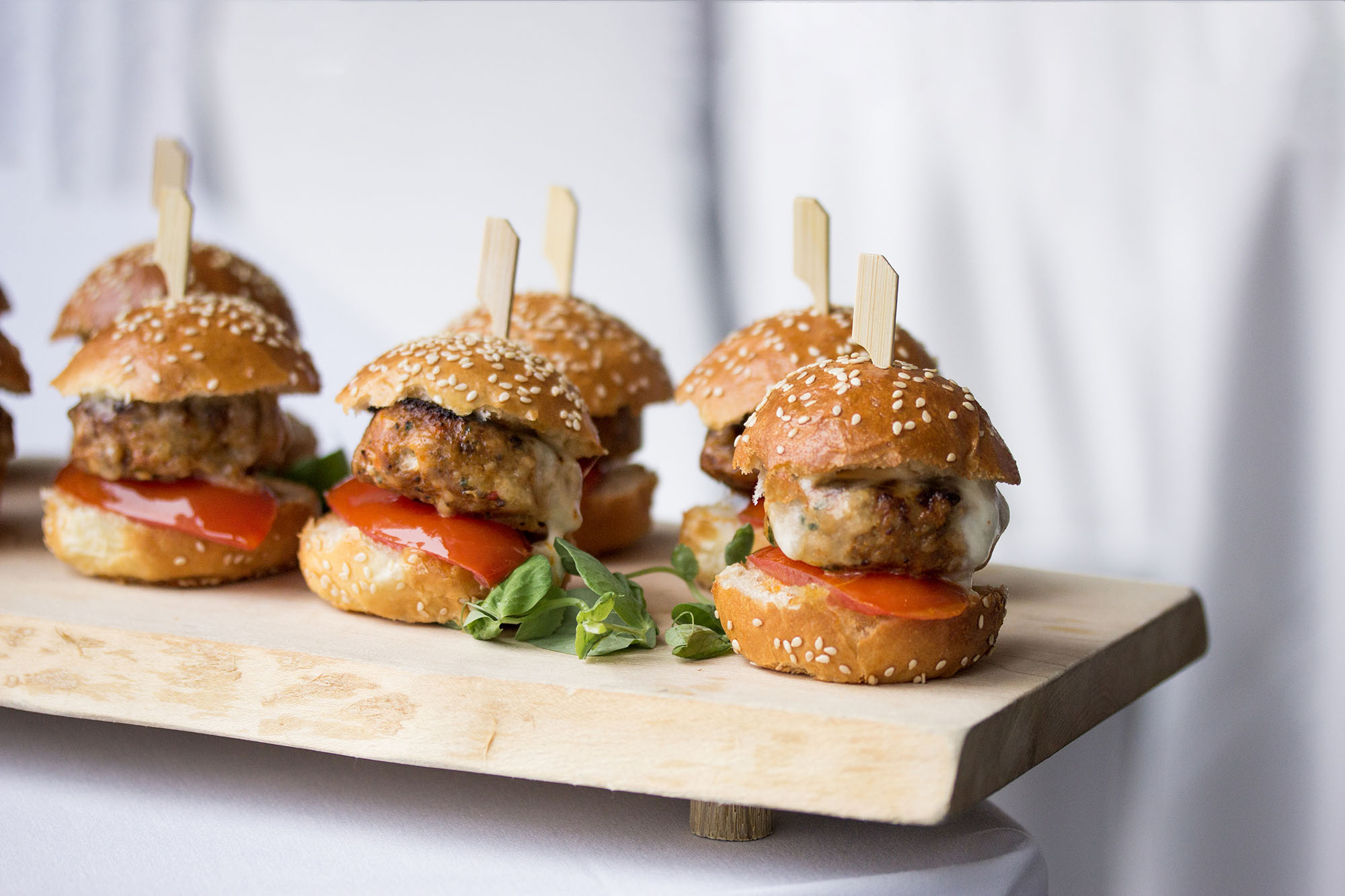 An assortment of sliders sitting on a wooden board
