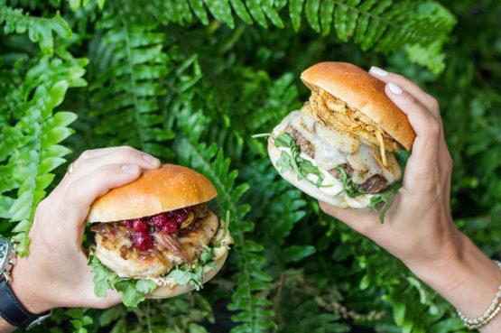 Turducken Burger and Mushroom and Swiss Beef Burger held in front of greenery