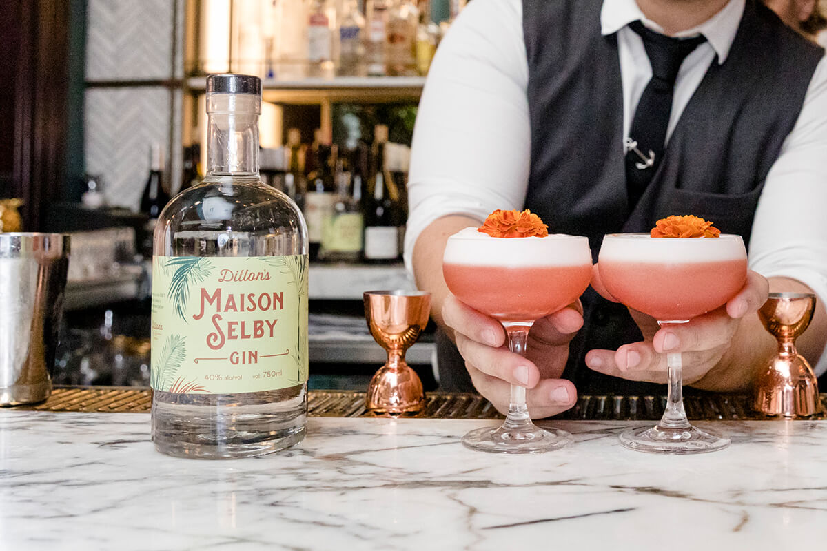 Bartender holding two cocktails at Maison Selby in Toronto