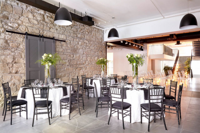 Seated event with black chairs and white table cloths at The Pioneer in Calgary