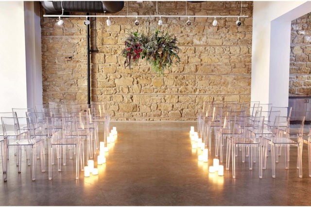 Pioneer Centre wedding aisle against a brick wall backdrop with clear chairs