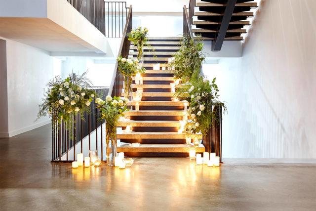 Staircase wrapped in greenery and candles at The Pioneer in Calgary