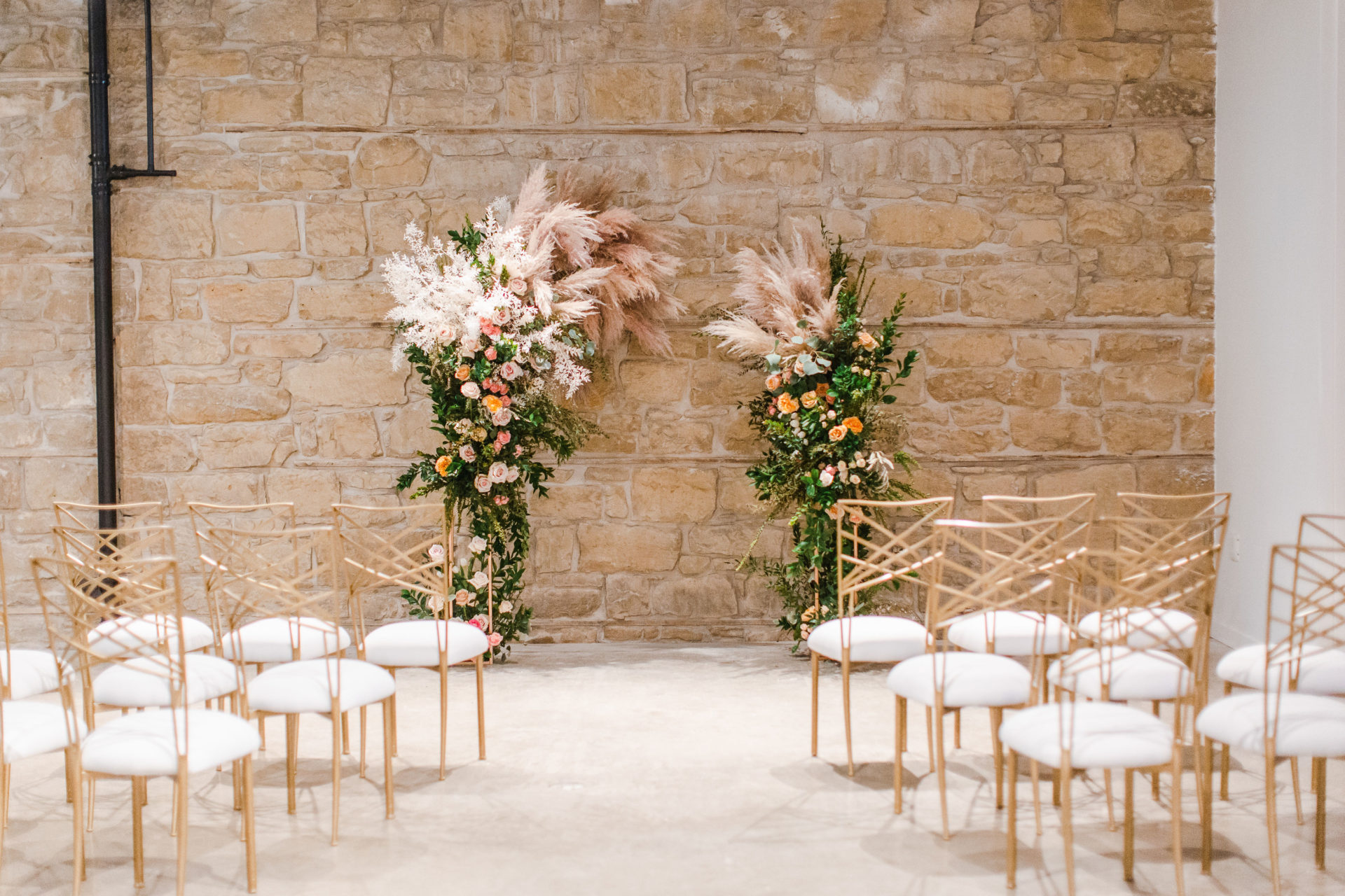 Floral wedding archway and gold chairs at The Pioneer event venue