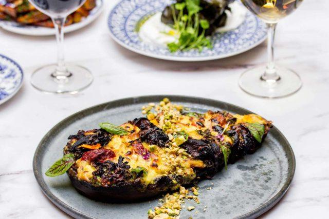 whole stuffed eggplant on a light grey plate