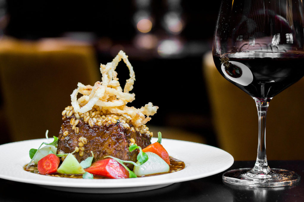 From Braised Short Ribs topped with crispy onions on a white plate, and a glass of red wine