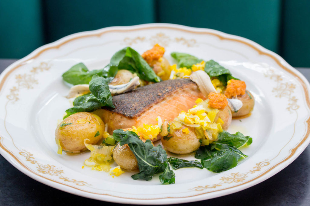 Salmon, mini potatoes and wilted greens on a white plate at Leña