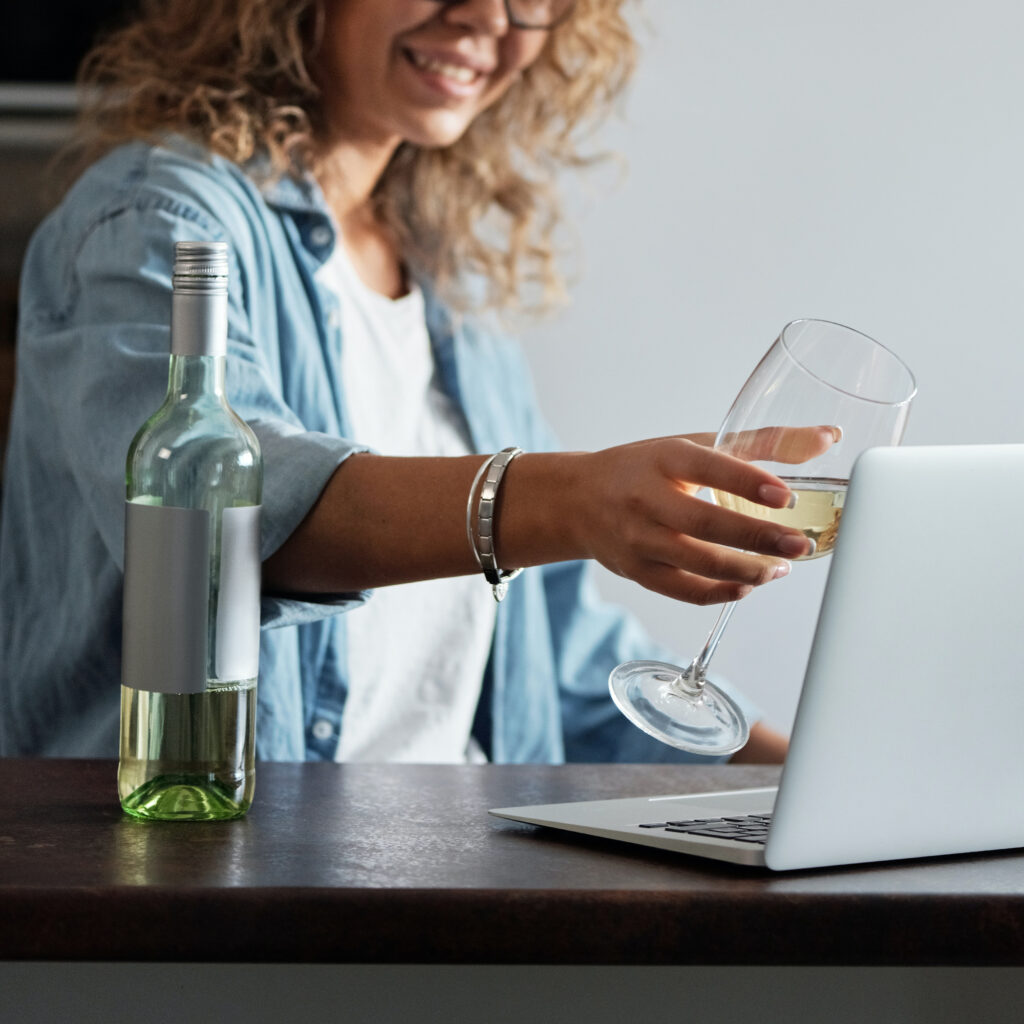 Woman on her computer drinking with over Zoom